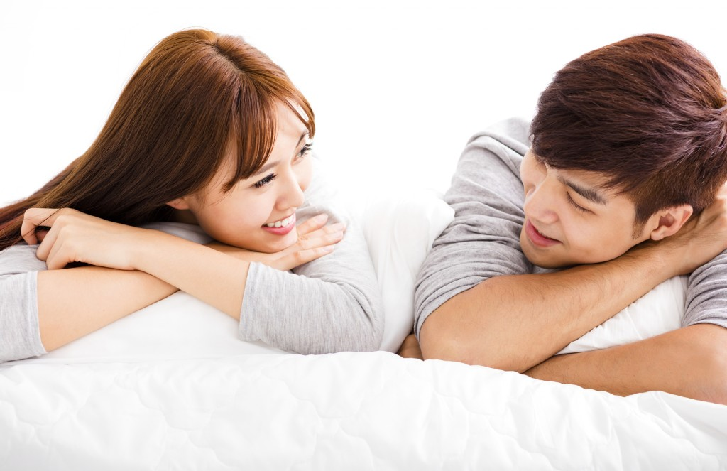 happy young couple lying in a bed