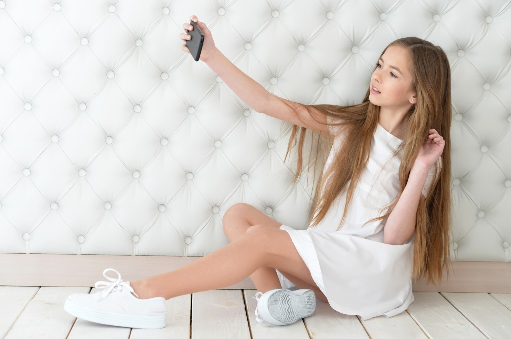 Pretty girl taking selfie with her smart phone