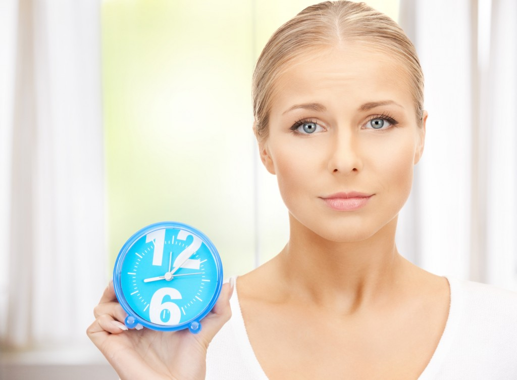 bright picture of woman holding alarm clock