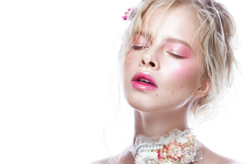 Beautiful blond fashion girl with flowers on neck and in her hair, wet Nude makeup. Beauty face.