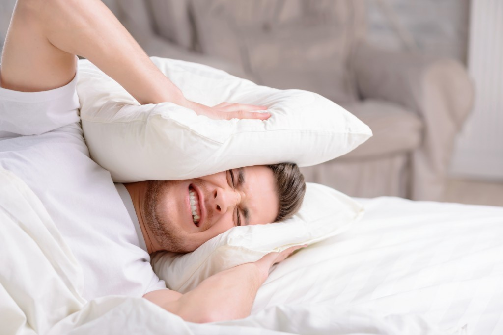 Stupid alarm. Handsome young man feels stressed when hides his head in pillows when irritating and loud alarm clock goes off.