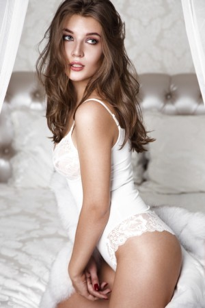 Beautiful sexy long-haired woman in white lingerie posing in the interior. The beauty of the face and body.